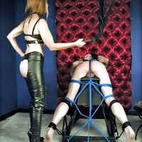 Two dominatrix in black latex whipping and biting roped male slave's ass cheeks