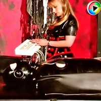 Latex mistress dominating over her rubber male sub in her dark dungeon