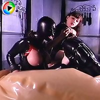 Heartless mistress punishes two bondaged female slaves in latex suits