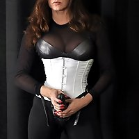 Beautiful mistress Jane posing in her white corset and huge strapon.