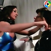 Mistress puts on latex suits on two lesbian slaves preparing them for a session